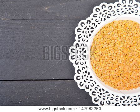 Red lentils on white plate with black wooden background