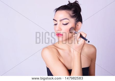 Closeup Of Young Hispanic Woman Applying Makeup