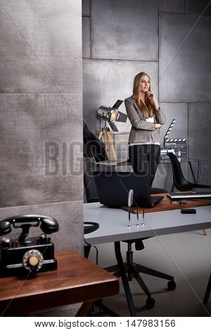 Young woman standing in studio, thinking.