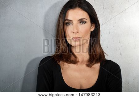Closeup portrait of serious young woman looking at camera.