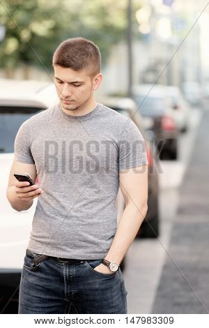 Outdoor portrait of young man in urban context with mobile phone