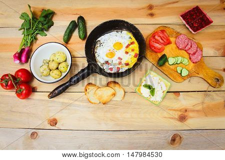 Different food: scrambled eggs in frying pan, boiled potatoes, curd, croutons, radishes, cucumbers, tomatoes, smoked sausage, mint, sorrel on wooden table.
