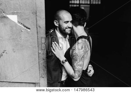 man and woman hugging in the doorway of an abandoned building