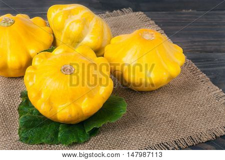yellow squash on a wooden background with a napkin of burlap.