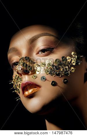 Young beautiful woman with art make up with golden thumbtacks