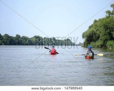 Two men in a kayak in the calm summer Danube river