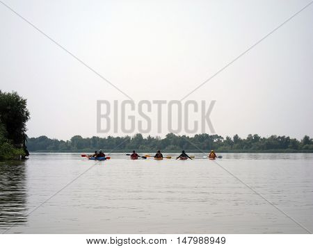 Five people in kayak canoeing along the Danube river on a summers day