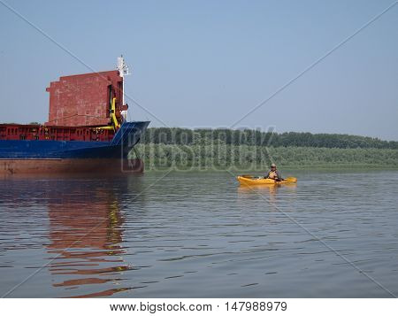 Man in yellow kayak and yellow rescue jacket on the calm blue Danube river in summer sunny day