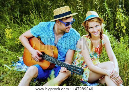 Enamored young man with a guitar singing his beloved girlfriend. They are sitting together on a lawn on a sunny summer day. Love concept.