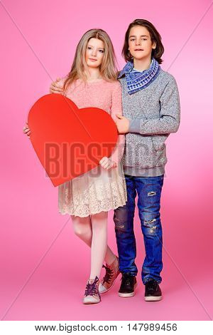 Full length portrait of happy teenage boy and girl holding red heart over pink background. Friendship. First love. Valentine's Day.
