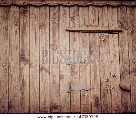 Small old wooden door of village well dark vertical boards. Vintage effect.