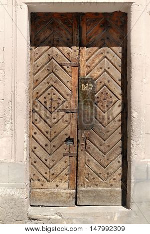 Old wooden door with wrought iron rivets in stone building
