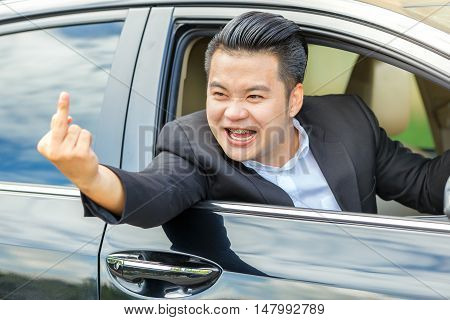 Asian young man driving a car and showing the middle finger