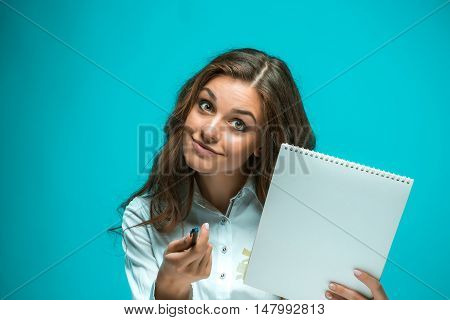 Surprised young business woman with pen and tablet for notes on a blue background