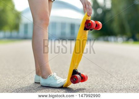 skateboarding, leisure, extreme sport and people concept - close up of teenage girl legs with short modern cruiser skateboard on road