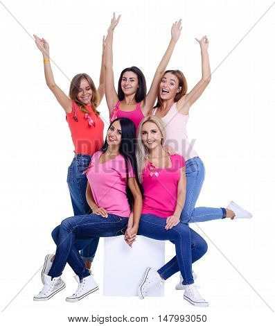 voluntary young women posing on white background and wearing pink for breast cancer