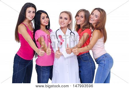 Smiling women in pink outfits showing thumbs up for breast cancer awareness on white background
