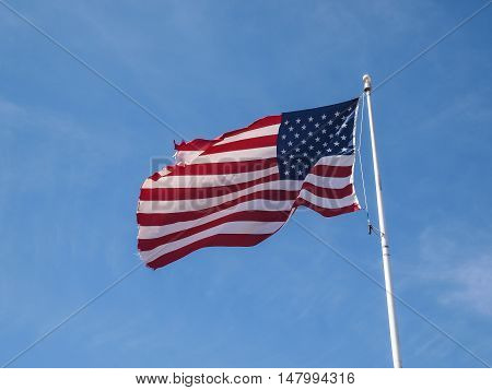 Tattered American Flag in the blue sky