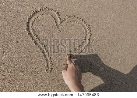 Woman's hand drawing a heart in the sand