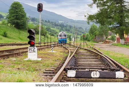 Old train railroad tracks traffic lights and other railway equipment on the provincial railway station in the Carpathian mountains at summer evening