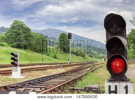 Railroad tracks and other railway equipment with traffic light glows red on the foreground on the provincial railway station in the Carpathians at summer evening