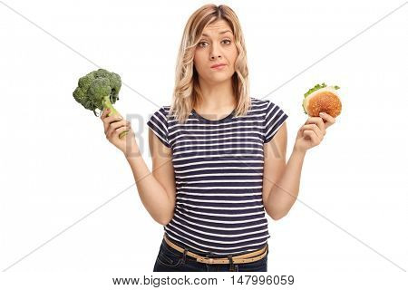 Hesitant woman holding a sandwich and broccoli isolated on white background