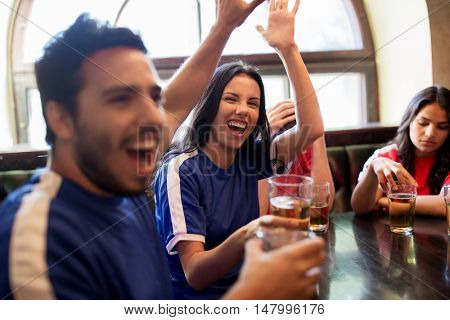 sport and entertainment concept - happy football fans or friends drinking beer, making high five and celebrating victory at bar or pub, supporting two teams with different shirt color