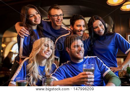 sport, people, leisure, friendship and entertainment concept - happy football fans or friends drinking beer at bar or pub