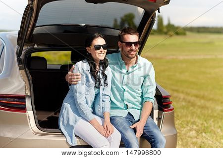 travel, summer vacation, road trip, leisure and people concept - happy couple hugging at open trunk of hatchback car outdoors