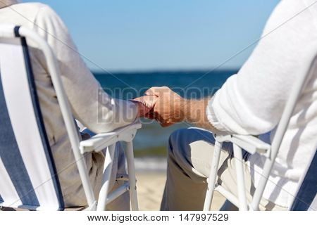 family, old age, travel, tourism and people concept - close up of happy senior couple sitting on deck chairs on summer beach