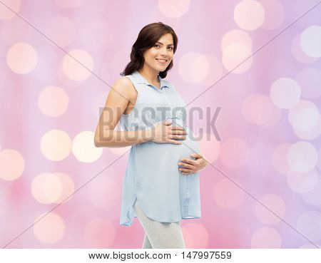 pregnancy, motherhood, people and expectation concept - happy pregnant woman touching her big belly over rose quartz and serenity holidays lights background