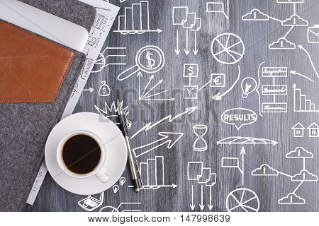 Top view of wooden desktop with creative white business doodles coffee cup electronic device in case and pen