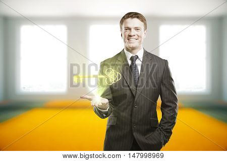 Handsome smiling businessman in suit holding shining golden ornate key on blurry interior background