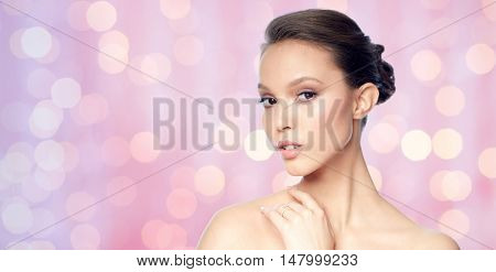 beauty, jewelry, accessories, people and luxury concept - face of beautiful young asian woman with golden ring over rose quartz and serenity lights background
