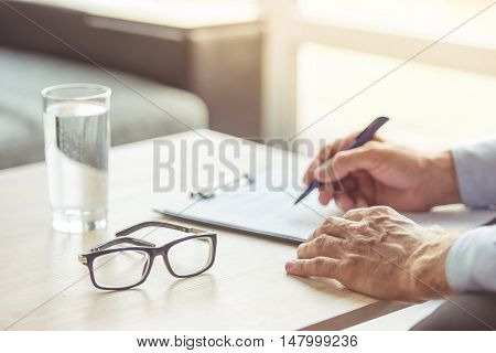 Hands of the middle aged psychotherapist are making notes glass of water and eyeglasses are near on the table