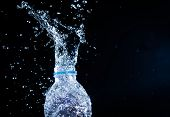 Water Splashes From The Bottle On Black Background poster
