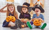 Happy brother and two sisters on Halloween. Funny kids in carnival costumes indoors. Cheerful childr poster