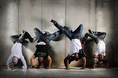 Hip Hop men performing dance with handstand over grunge background
