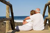 rear view of senior couple cuddling on beach