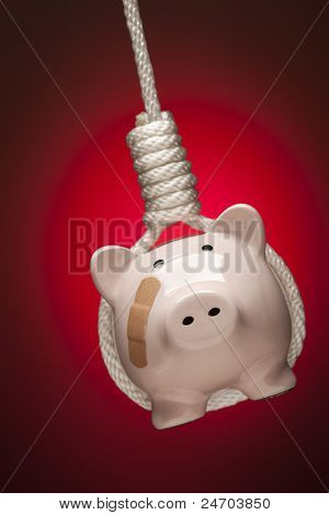 Piggy Bank with Bandage Hanging in Hangman's Noose on Red Spot Lit Background.