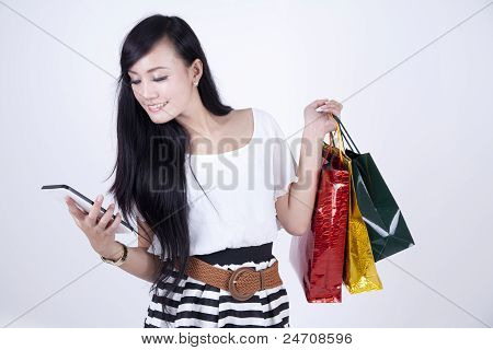 Asian Woman Looking At Her Computer Tablet While Carrying Gift Bags
