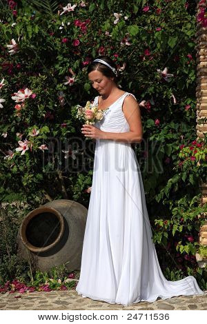 Bride Looking At Her Bouquet In A Garden