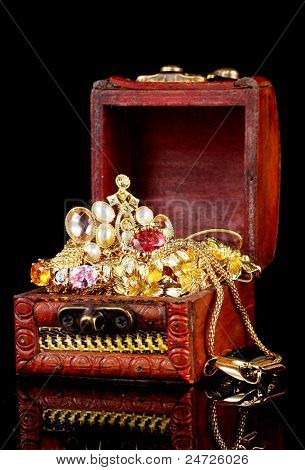 Wooden chest full of gold jewelry on black background