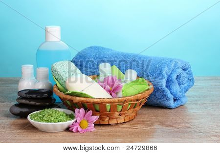 Hotel amenities kit in basket on wooden table on blue background
