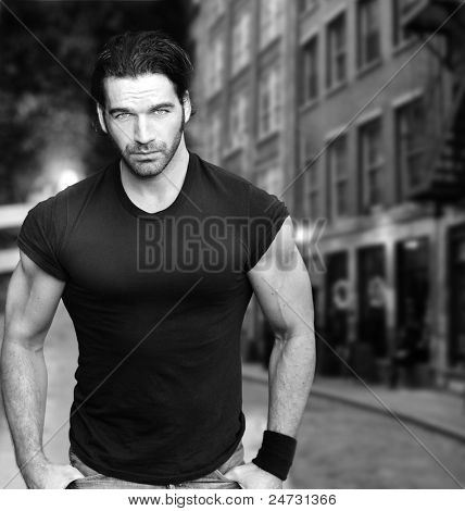 Vintage stylized black and white photo of young male model against city street