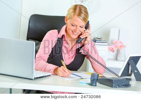 Smiling Business Woman Talking Phone And Writing At Notepad