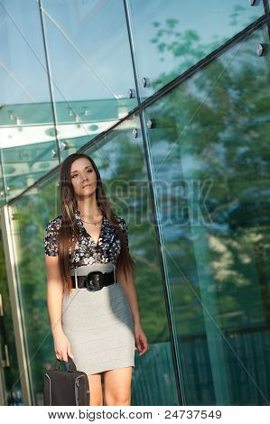 brunette walking along glass wall