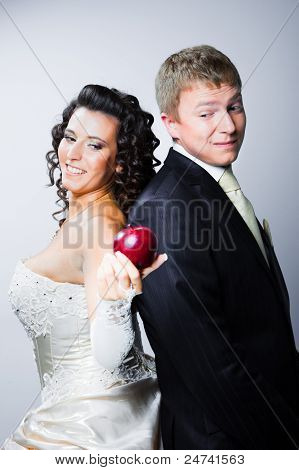 Bride Offering A Red Apple To Doubting Groom