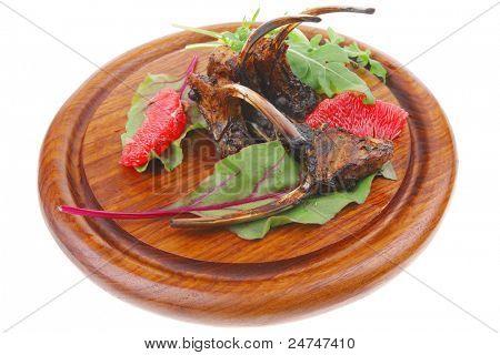 Hauptteil: gegrillte Rippen auf Woden Platte isoliert auf weißem Hintergrund mit Salat Blätter und rot