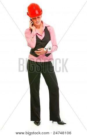 Full Length Portrait Of Modern Architect Woman With Flipcharts Talking Mobile